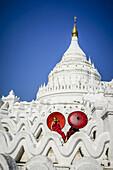 Asian monks sitting under umbrellas at historic temple, Mingun, Mandala, Myanmar, Mingun, Mandalay, Myanmar