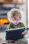 Caucasian baby boy using digital tablet, C1