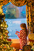 Caucasian girl opening present near Christmas tree, C1
