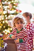 Caucasian baby boy opening present near Christmas tree, C1