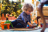 Caucasian baby boy playing with toys near Christmas tree, C1