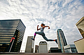 African American woman leaping on urban rooftop, Los Angeles, California, USA
