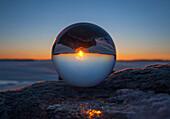 Close up of sunset horizon inverted in glass sphere, Gananoque, Ontario, canada