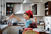 A little boy is preparing a chocolate cake and takes a egg