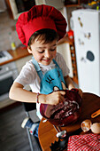 A little boy cooking a chocolate cake