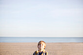 Portrait of a young boy with eyes closed at the beach