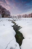 France, Aquitaine, Pyrenees, Atlantiques, Puddle of water in the middle of a snow-covered field during sunset