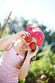 Girl holding up tomatoes up to her eyes and sticking out one's tongue