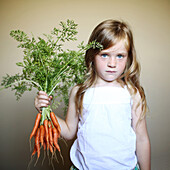 Little girl holding some carrots