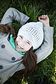 Portrait of a 7 years old girl, she is lying in the grass