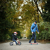 A 3 years old little boy on bike going with his father on skateboarding in a park