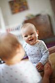 A 10 months baby girl smiling in front of a mirror