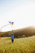 Asian woman flying kite in field