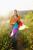 Hispanic woman holding kite outdoors