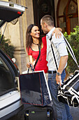 Couple loading luggage and bags into car