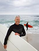 Senior man holding surfboard at beach