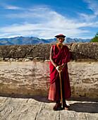 Elderly Tibetan monk with walking stick