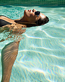 Hispanic woman floating in swimming pool