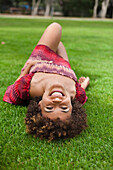 Smiling mixed race woman laying in grass