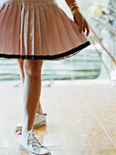 Woman in skirt and sneakers