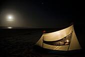 Caucasian man camping on beach
