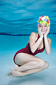 Smiling Caucasian woman wearing vintage bathing suit and cap underwater