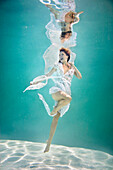 Caucasian woman in elegant dress under water