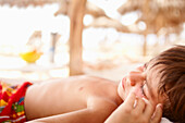 Sleeping mixed race boy laying on beach