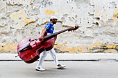 Hispanic musician carrying bass on city street
