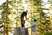 Couple playing on tree stump in forest