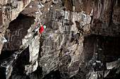 Asian climber scaling steep cliff face