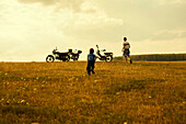 Boys running to motorcycles in rural landscape