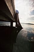 Caucasian woman dipping feet in still lake