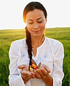Asian woman holding butterfly in hands