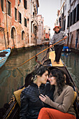Romantic Italian couple riding in gondola through canal