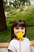 Mixed race girl holding star wand