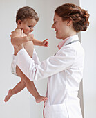 Pediatrician lifting child