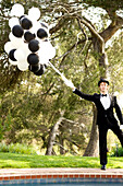 Caucasian man in tuxedo holding bunch of balloons