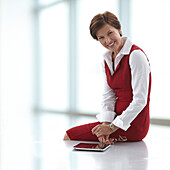 Caucasian businesswoman sitting on table with digital tablet