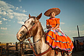Hispanic woman in traditional dress on horse