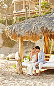 Newlywed couple relaxing in cabana