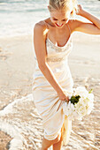 Caucasian bride holding bouquet on beach