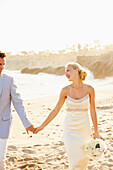Newlywed couple walking on beach