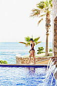 Caucasian woman walking along swimming pool