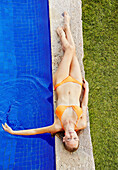 Caucasian woman relaxing by swimming pool