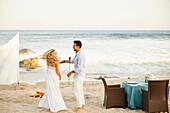 Newlywed couple dancing on beach