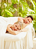Couple laying on massage tables outdoors
