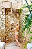 Caucasian woman showering outdoors