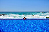 Mixed race woman relaxing in infinity pool