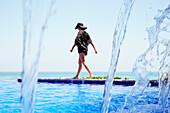 Mixed race woman walking along infinity pool